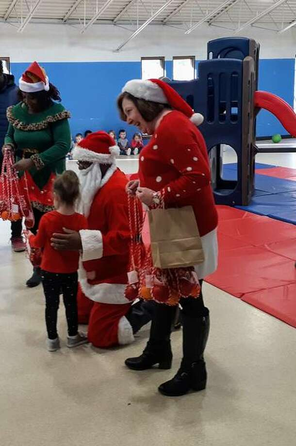 State Rep. Monica Bristow and Rosetta Brown help Santa hand out treats to the kids at St. Francis Daycare at St. Anthony's Hospital in Alton on Monday.