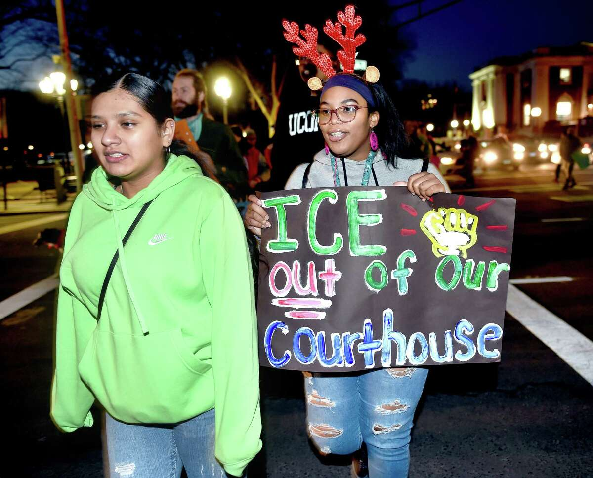 Wilbur Cross High School students Angeli Arevalo (left), 17, and Dajia Carr, 17, participate in a rally for classmate Mario Aguilar, 18, who was being held in detention by ICE in Boston, as it moves from Superior Court to City Hall in New Haven on December 23, 2019.