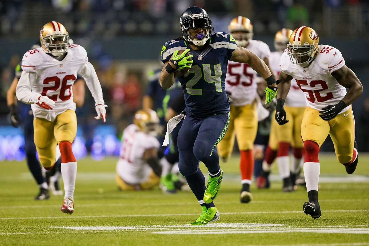 FILE - Seahawks running back Marshawn Lynch, center, pushes through 49ers defense during the first half of the NFC Championship game Sunday, Jan. 19, 2014, at CenturyLink Field in Seattle.