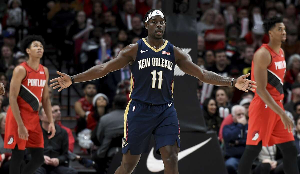 New Orleans Pelicans guard Jrue Holiday, center, reacts after making a shot as Portland Trail Blazers guard Anfernee Simons, left, and center Hassan Whiteside, right, walk nearby during the second half of an NBA basketball game in Portland, Ore., Monday, Dec. 23, 2019. The Pelicans won 102-94. (AP Photo/Steve Dykes)