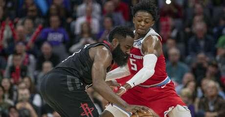 Houston Rockets guard James Harden (13) and Sacramento Kings guard De'Aaron Fox (5) vie for control of the ball during the second half of an NBA basketball game in Sacramento, Calif., Monday, Dec. 23, 2019. The Rockets won 113-104. (AP Photo/Randall Benton)