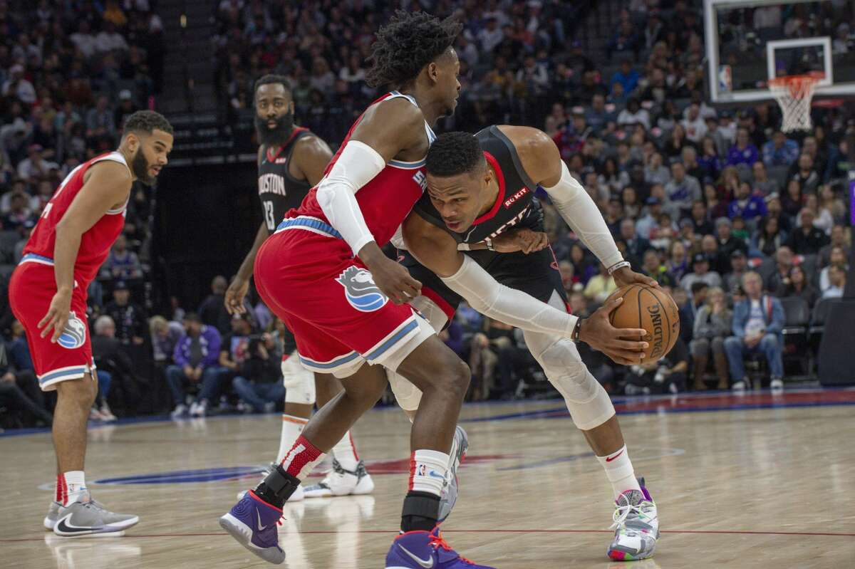 Sacramento Kings guard De'Aaron Fox defends against Houston Rockets guard Russell Westbrook during the second half of an NBA basketball game in Sacramento, Calif., Monday, Dec. 23, 2019. The Rockets won 113-104. (AP Photo/Randall Benton)