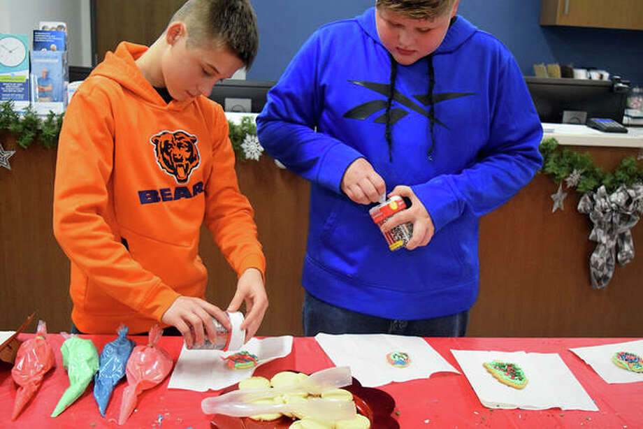Wyatt Raymond (left), 11, and Jesse Raymond, 12, both of Jacksonville, decorate Christmas cookies Monday at HSHS Medical Group Multispecialty Care.