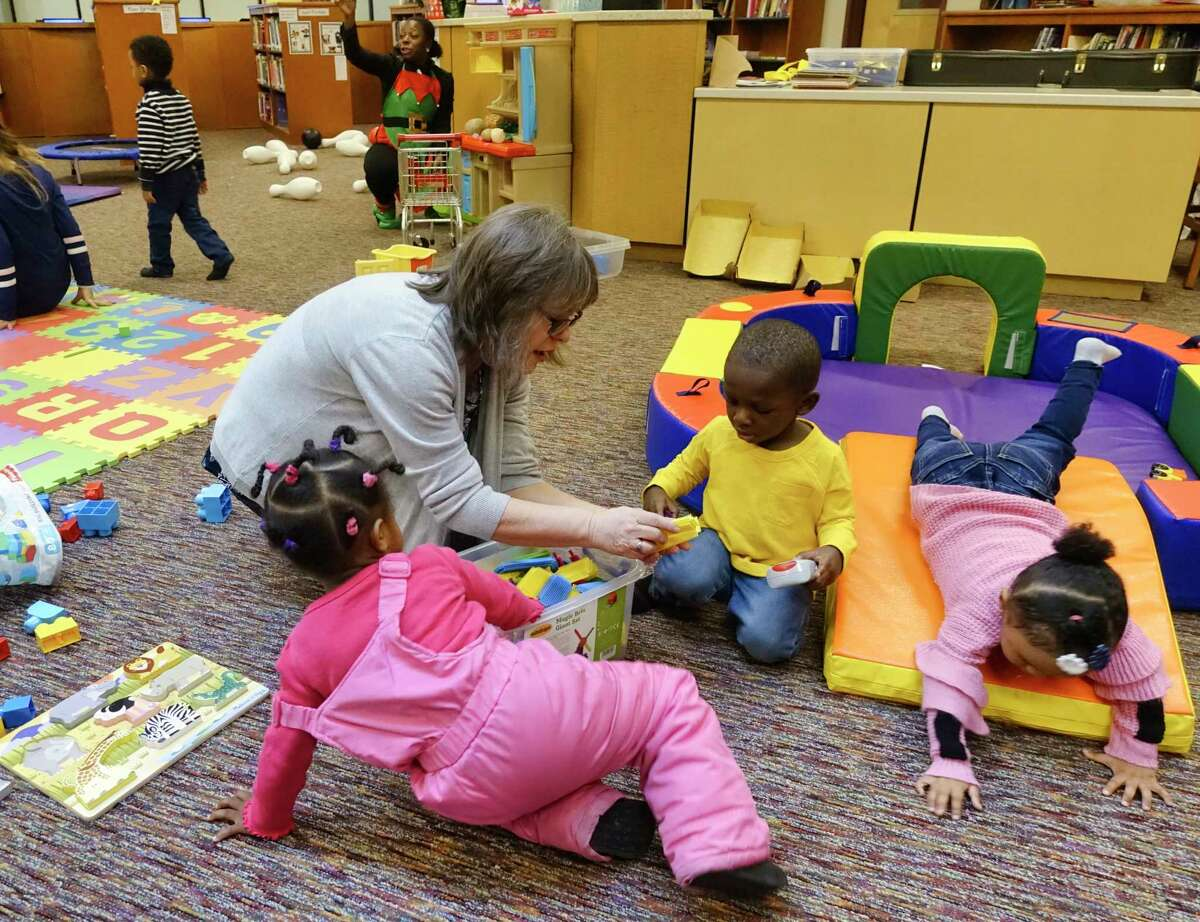 Lisa Momberger, the assistant early childhood coordinator for the Albany School District, plays with Milani Smith, 1, left, Jhalaun Williams, 2, center, and Aalissya Johnson, 2, at the Play, Learn, Soar program at Arbor Hill Elementary School on Tuesday, Dec. 17, 2019, in Albany, N.Y. (Paul Buckowski/Times Union)