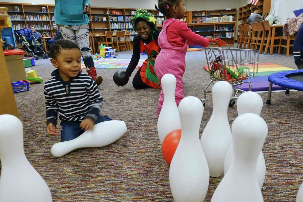 Shanae Lawrence, background center, the Arbor Hill Elementary Community School site coordinator, plays with Semaj Johnson, 4, left, and Milani Smith, 1, right, at the Play, Learn, Soar program at Arbor Hill Elementary School on Tuesday, Dec. 17, 2019, in Albany, N.Y. (Paul Buckowski/Times Union)
