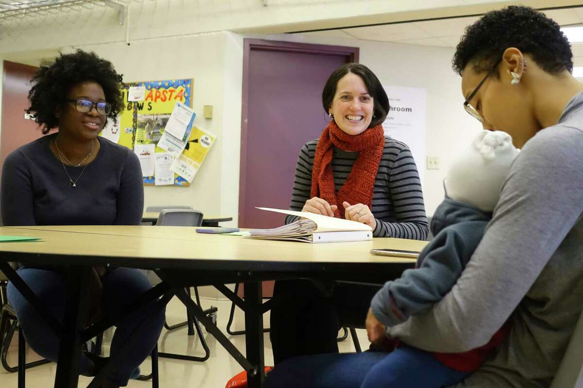 Maria DeLucia-Evans, center, association resource director for the Cornell Cooperative Extension, runs a parent workshop on supporting child development by creating a literacy program at home, for moms, Imani Francis, left, and Latisia Johnson, right, who is holding her son, Santigo Johnson, 5 months old, at the Play, Learn, Soar program at Arbor Hill Elementary School on Tuesday, Dec. 17, 2019, in Albany, N.Y. (Paul Buckowski/Times Union)