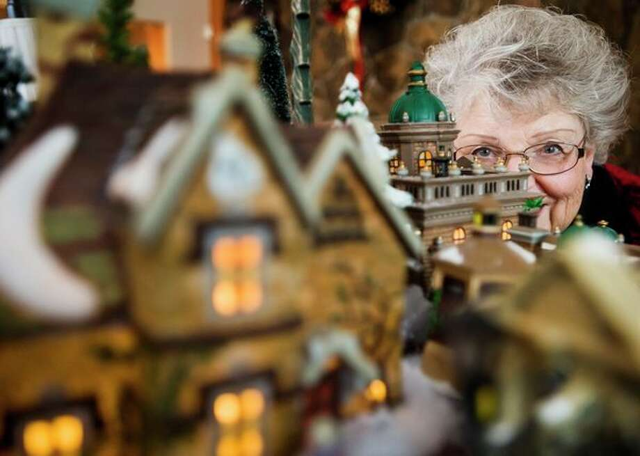 Kay Pfenninger poses for a portrait with her elaborate Dickens' Village collection Thursday at her home in Midland. (Katy Kildee/kkildee@mdn.net)