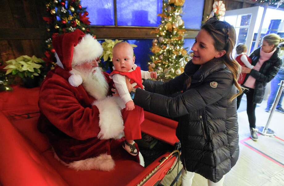 Rebecca O'Callaghan of Greenwich carefully hands Santa (Walter Kelly of Greenwich) nine-month-old Brooks as they pose for a holiday photo at Santa's Workshop at the Greenwich Reindeer Festival & Santa's Village at Sam Bridge Nursery & Greenhouses in Greenwich, Conn. on Dec. 19, 2019. With the upcoming holiday, the reindeer will be leaving to head back to the North Pole on Saturday and Santa and his band of Merry helpers will be closing on Christmas Eve. So if you want to get those last minute holiday photos and pick up some joyful cheer, come visit the Festival & Santa's Village. For times and other information visit: https://www.greenwichreindeerfestival.com Photo: Matthew Brown / Hearst Connecticut Media / Stamford Advocate