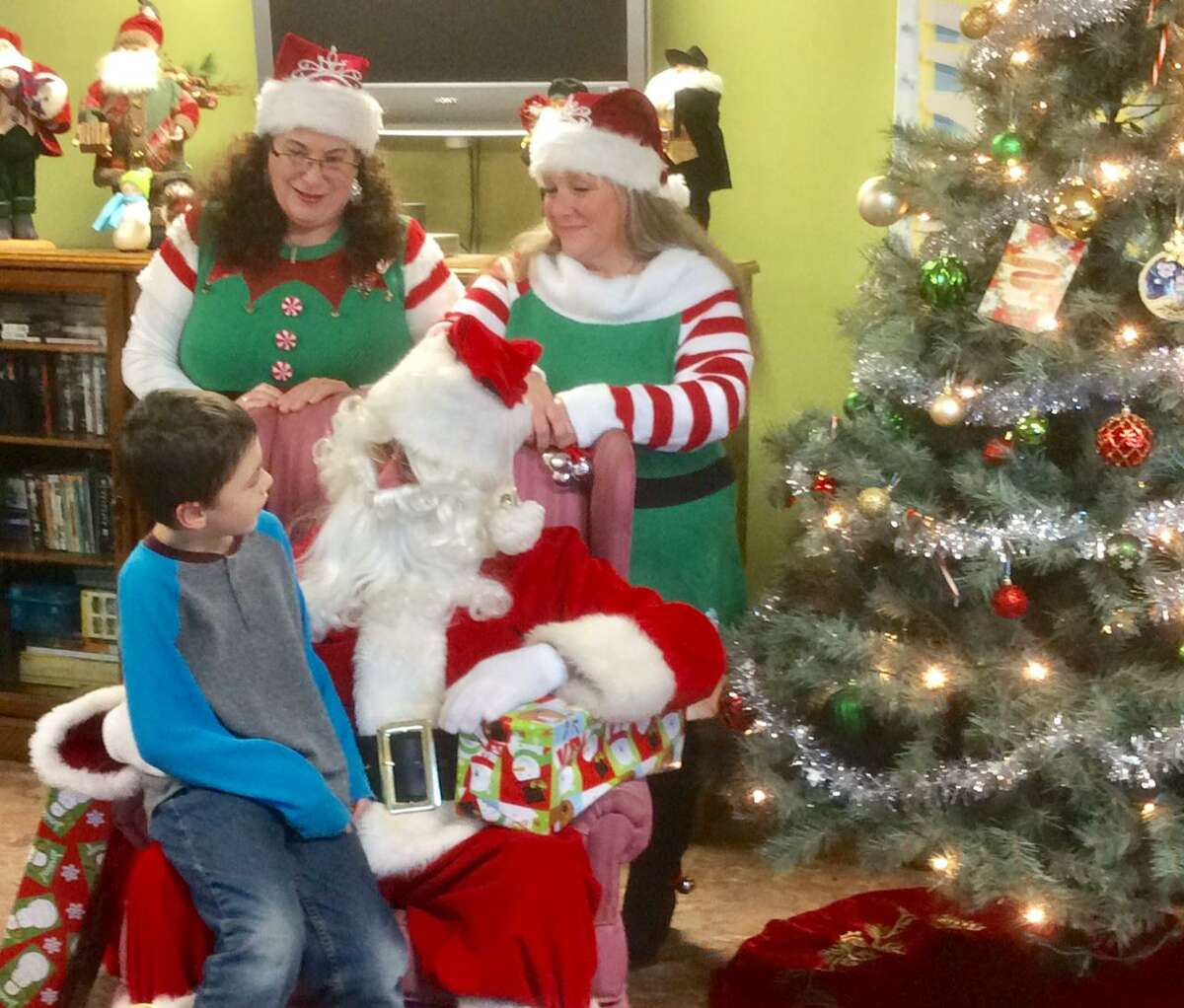 FISH held its Cookies & Cocoa party for the shelter's children on Dec. 20. Above, staff members dressed as elves join Santa to hear a little boy's Christmas wishes.
