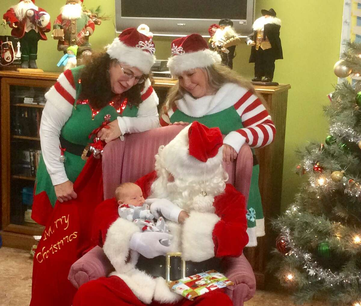 Santa Claus holds the FISH shelter's youngest resident - an 8-day-old baby, during the shelter's Cookies & Cocoa party for the shelter's children.