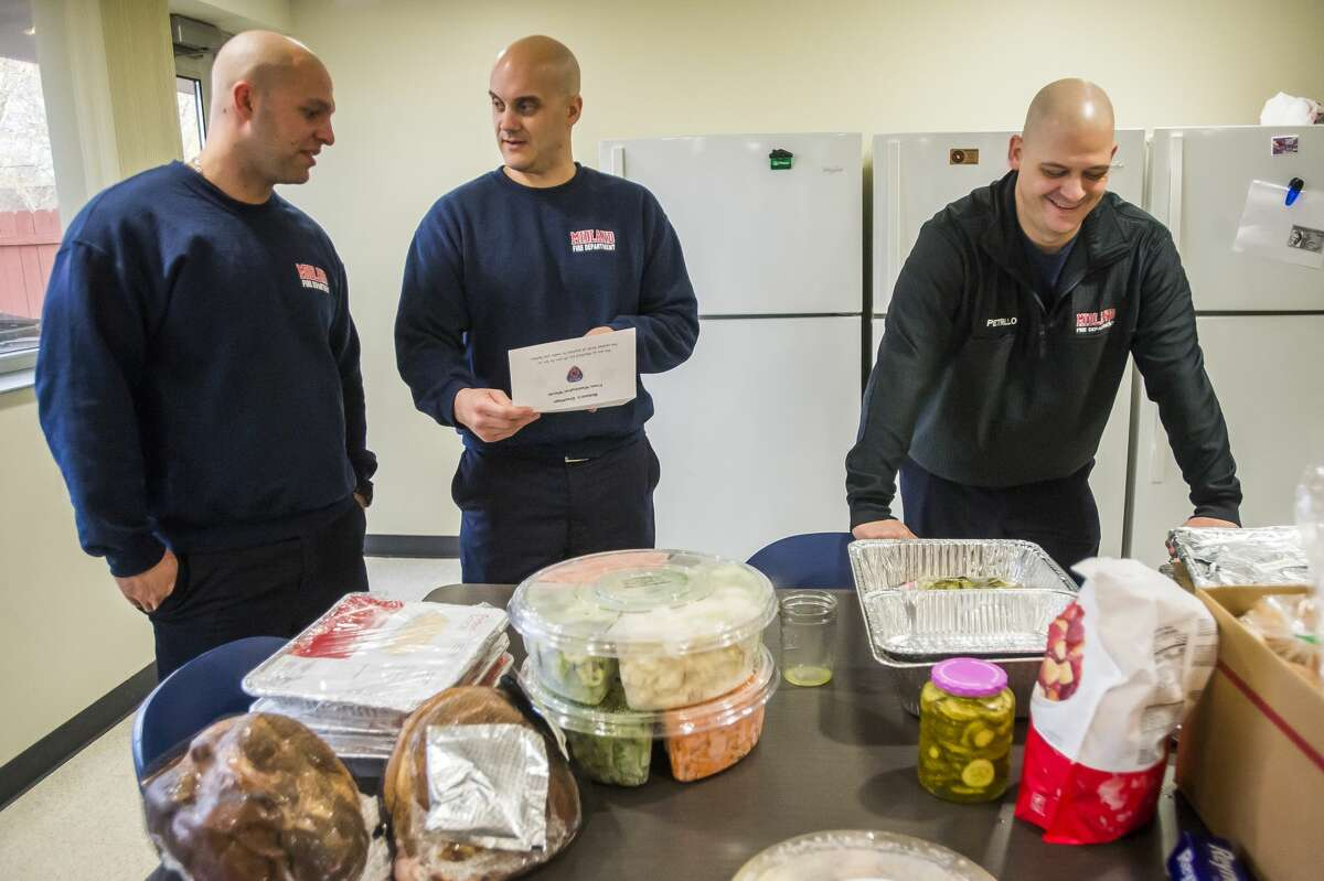 From left, City of Midland firefighters Cam Gelinas, Dave Danek and Nick Petrillo read a card that was delivered as part of a large donation of food from residents of Washington Woods Tuesday, Dec. 24, 2019 at fire station #1. (Katy Kildee/kkildee@mdn.net)