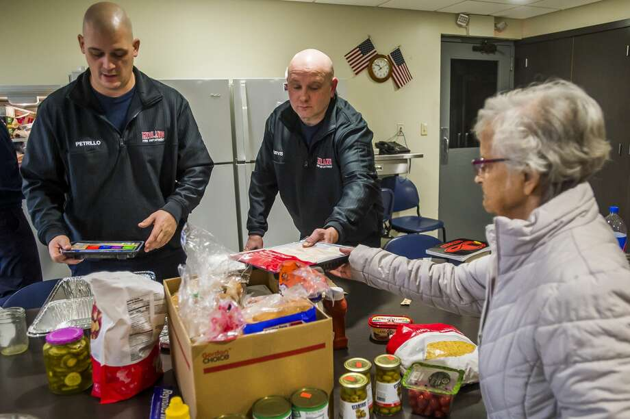City of Midland firefighters Nick Petrillo, left, and Justin Purvis, center, accept a large donation of food from residents of Washington Woods, including Dolores Davis, right, Tuesday, Dec. 24, 2019 at fire station #1. (Katy Kildee/kkildee@mdn.net) Photo: (Katy Kildee/kkildee@mdn.net)