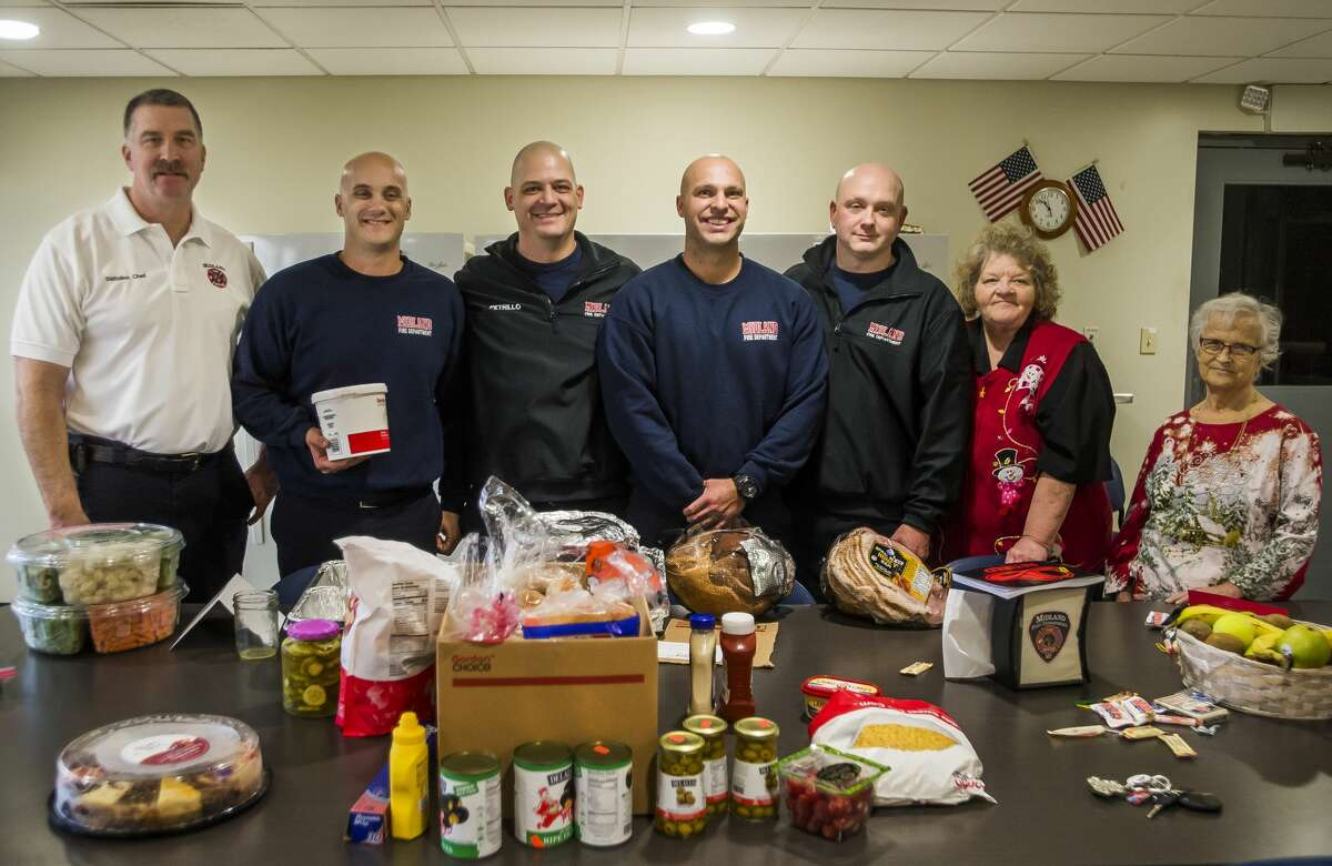 From left, City of Midland firefighters Mike Hulpert, Dave Danek, Nick Petrillo, Cam Gelinas and Justin Purvis pose for a photo with Washington Woods residents Cyndi Sanderson, second from right, and Dolores Davis, right, after the two women delivered a large donation of food to the fire station Tuesday, Dec. 24, 2019. (Katy Kildee/kkildee@mdn.net)