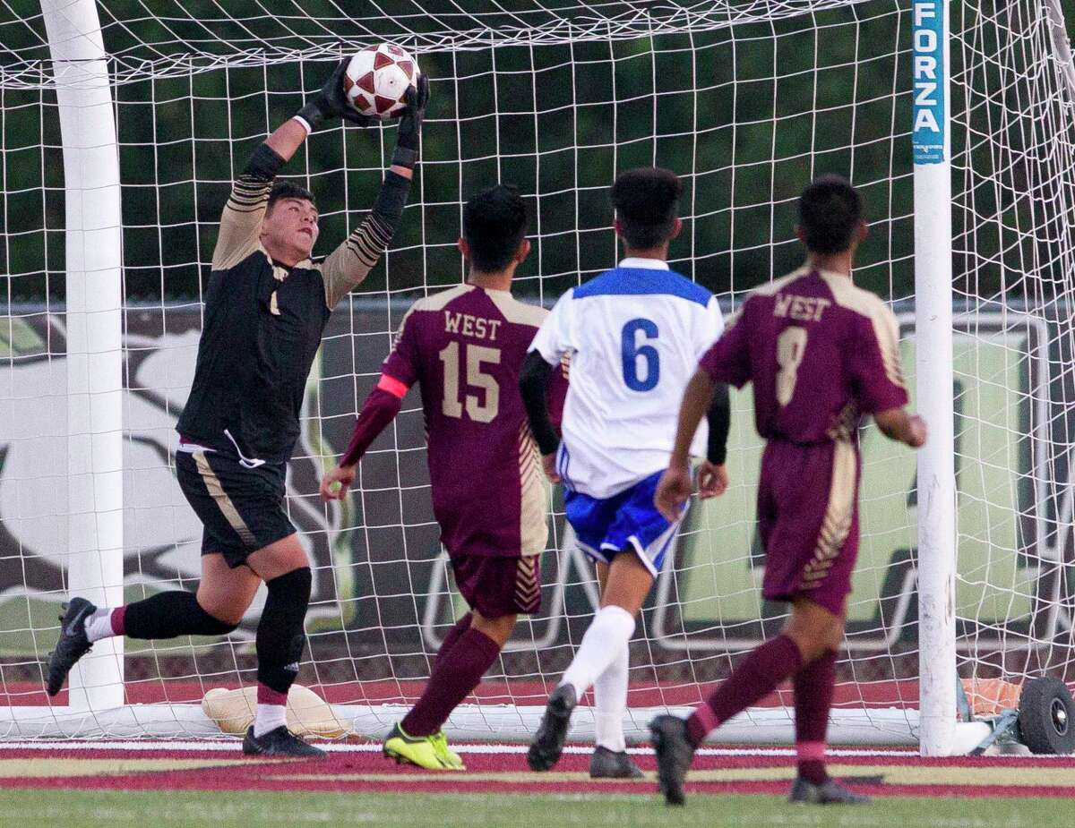 Magnolia West goalie Felix Martinez (1) makes a stop during the first period of a Region III-5A bi-district soccer match at Magnolia West West High School, Friday, March 29, 2019, in Magnolia.