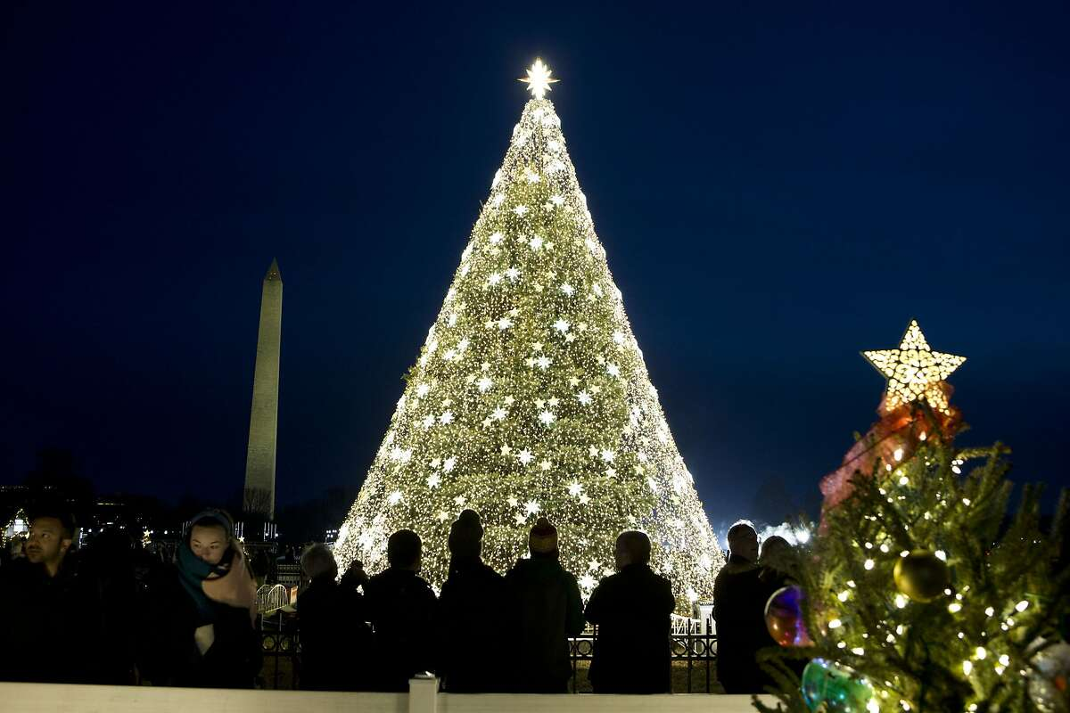 Visitors look at the National Christmas Tree with the Washington Monument in the background on the Ellipse near the White House, in Washington, Sunday, Dec. 22, 2019. ( AP Photo/Jose Luis Magana)
