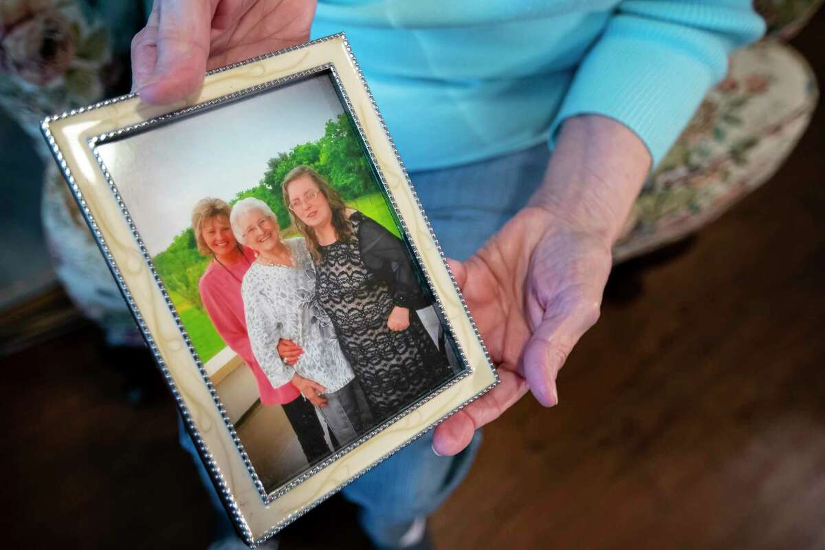 Dolly Davis holds a picture of herself with her daughters Cindy (right) and Shelly (left) after the funeral of Cindy's husband.