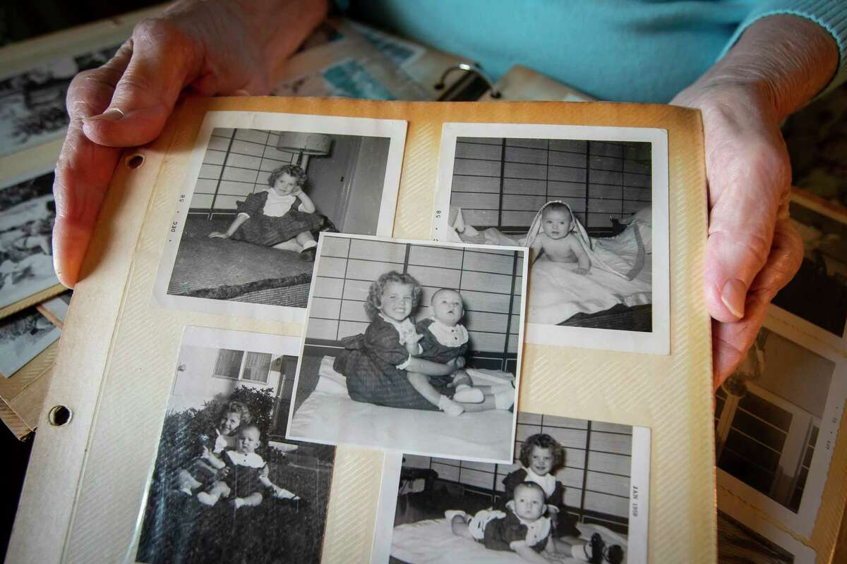 Dolly Davis holds pictures of her daughter Cindy as a 6-month-old in 1958, a day before an accident left Cindy partially paralyzed, in an album inside Davis' home in Huntsville, Thursday, Dec. 12, 2019. Davis has been urging Cindy, who has been living on the streets in Houston, to move in with her in Huntsville.