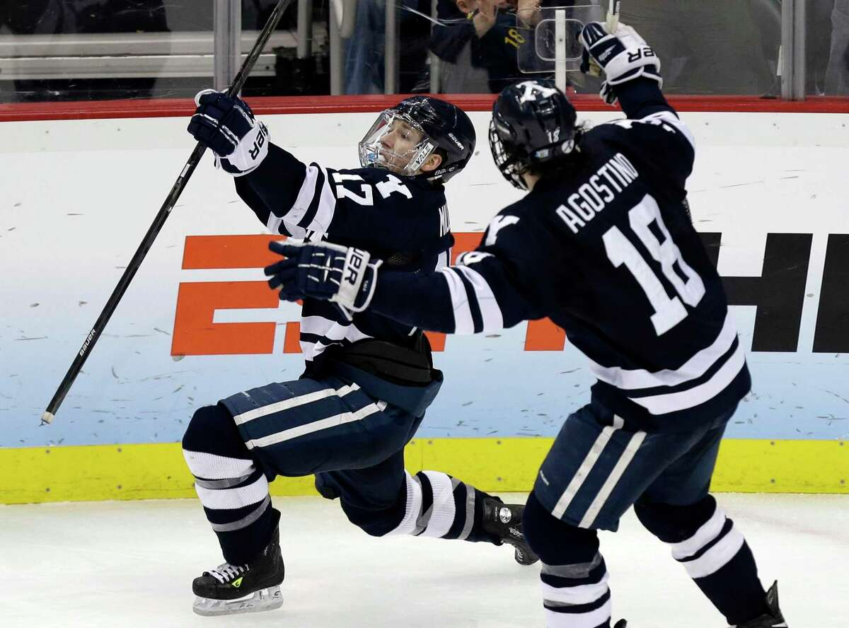 Yale's Andrew Miller (17) celebrates his winning goal against UMass Lowell with Kenny Agostino (18) during overtime of an NCAA Frozen Four college hockey semifinal in Pittsburgh, Thursday, April 11, 2013.