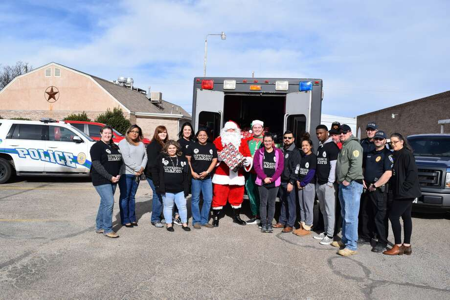 Plainview officers and their families gather Monday morning to deliver gifts to local foster families. Photo: Ellysa Harris/Plainview Herald