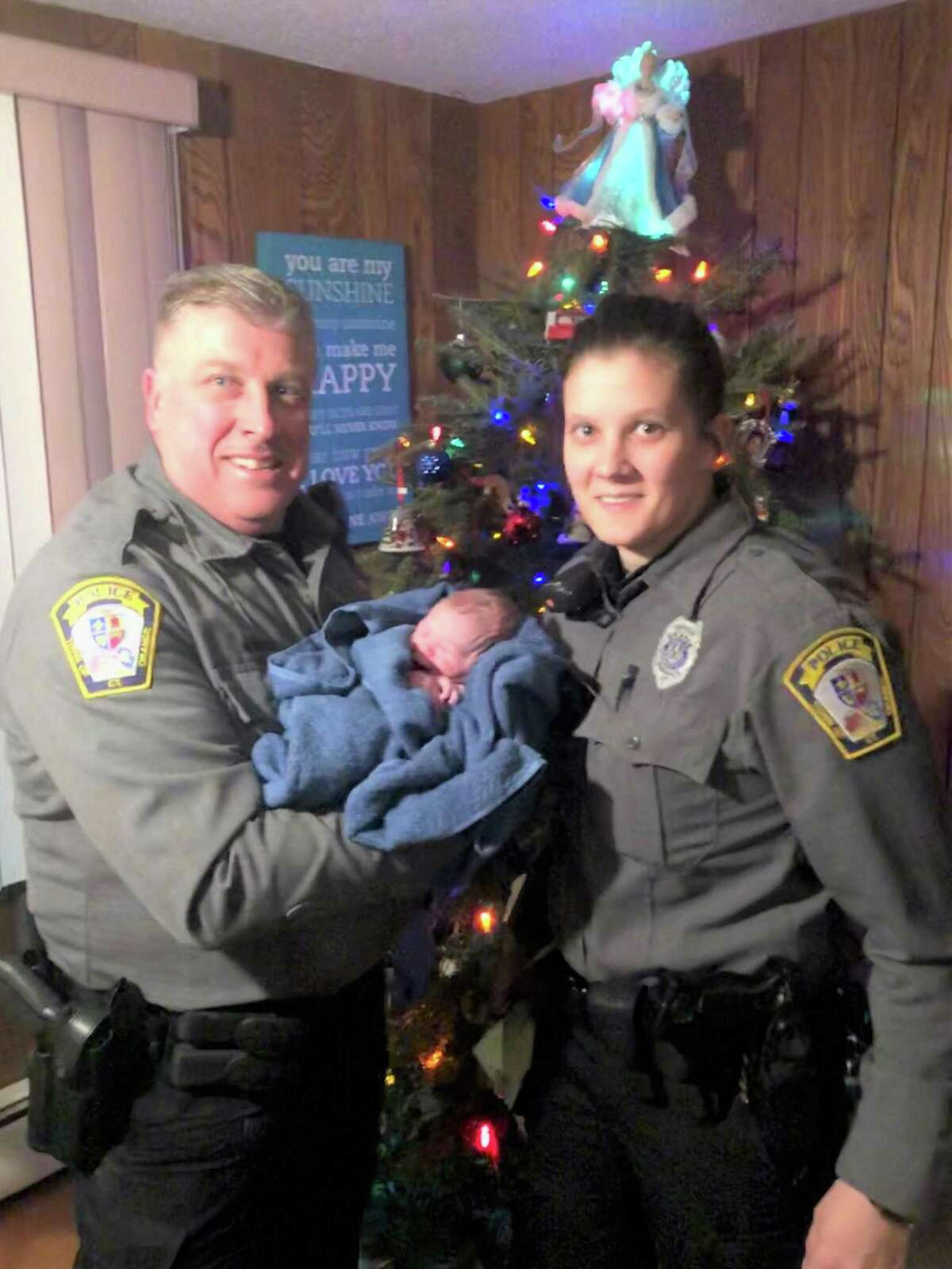 Police officer Frank Koshes, left and Officer Emily Taylor holding newborn bundle of joy, Jillian, who was born at home .