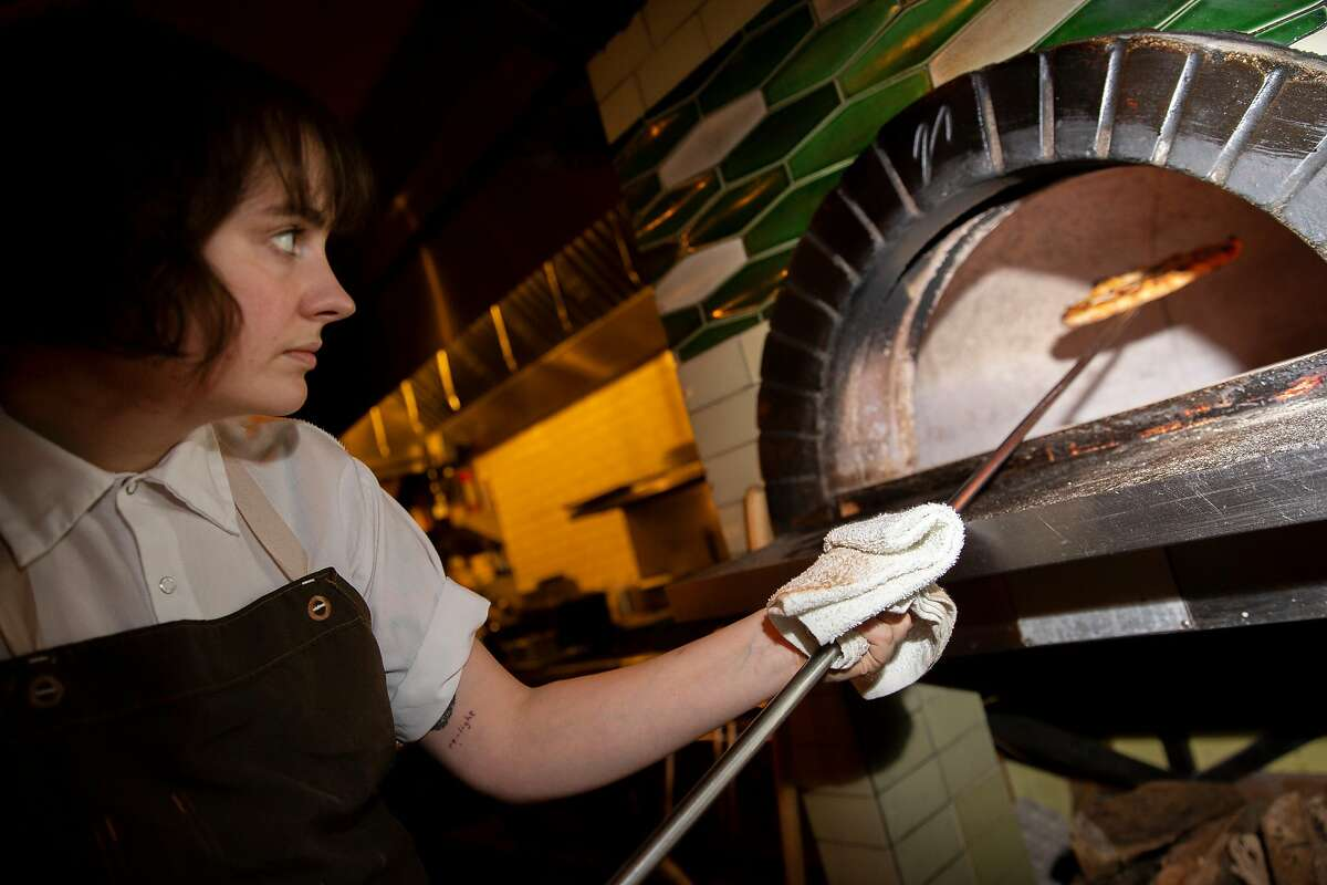 Madeline Kenney cooks a pizza at Sister on Thursday, Dec. 19, 2019, in Oakland, Calif. The restaurant is located at 3308 Grand Ave.