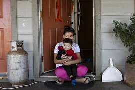 Angellee Ribas, 10, holds her baby brother, Fernando, 1, outside their apartment complex during the power outage. Ukiah, California.