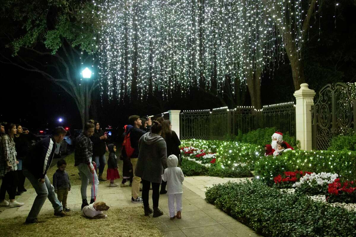 Visitors tour the Christmas lights decorating River Oaks Boulevard homes on Sunday, Dec. 22, 2019, in Houston.