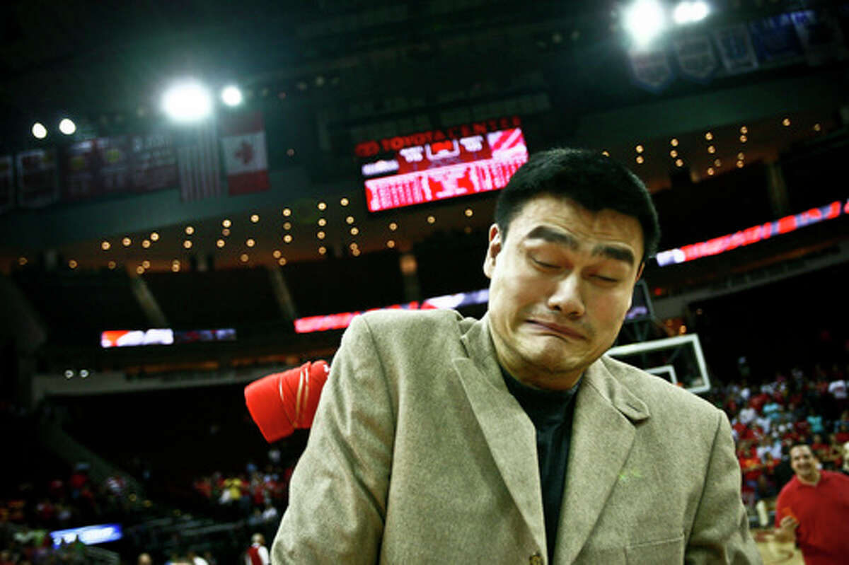 April 14, 2010: Houston Rockets center Yao Ming (11) gets hit by a shirt thrown by Clutch the mascot as he passes out gifts to fans during the Red Nation Appreciation Night after the Houston Rockets vs the New Orleans Hornets NBA basketball game at the Toyota Center in Houston. The Rockets lost the game 115-123.
