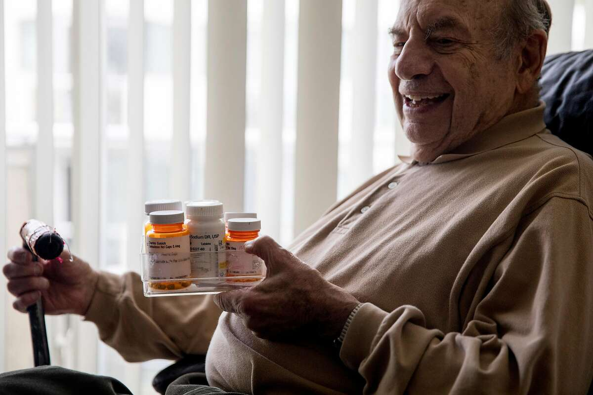 Charles Gusick hods his various daily medications while posing for a portrait his home in Mill Valley, Calif. Wednesday, December 24, 2019.