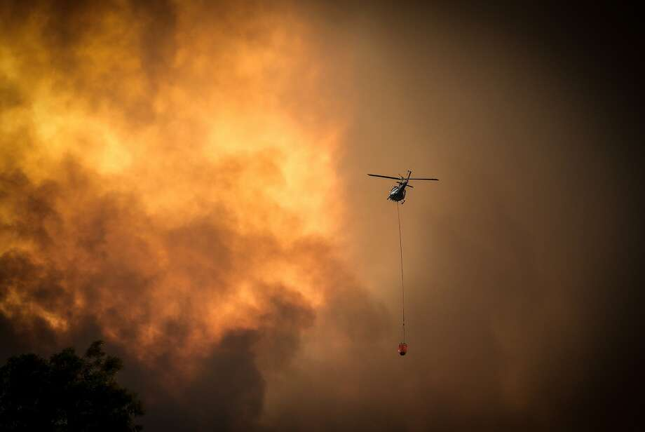Helicopters dump water on wildfires fires near Bargo, about 60 miles southwest of Sydney. Photo: David Gray / Getty Images