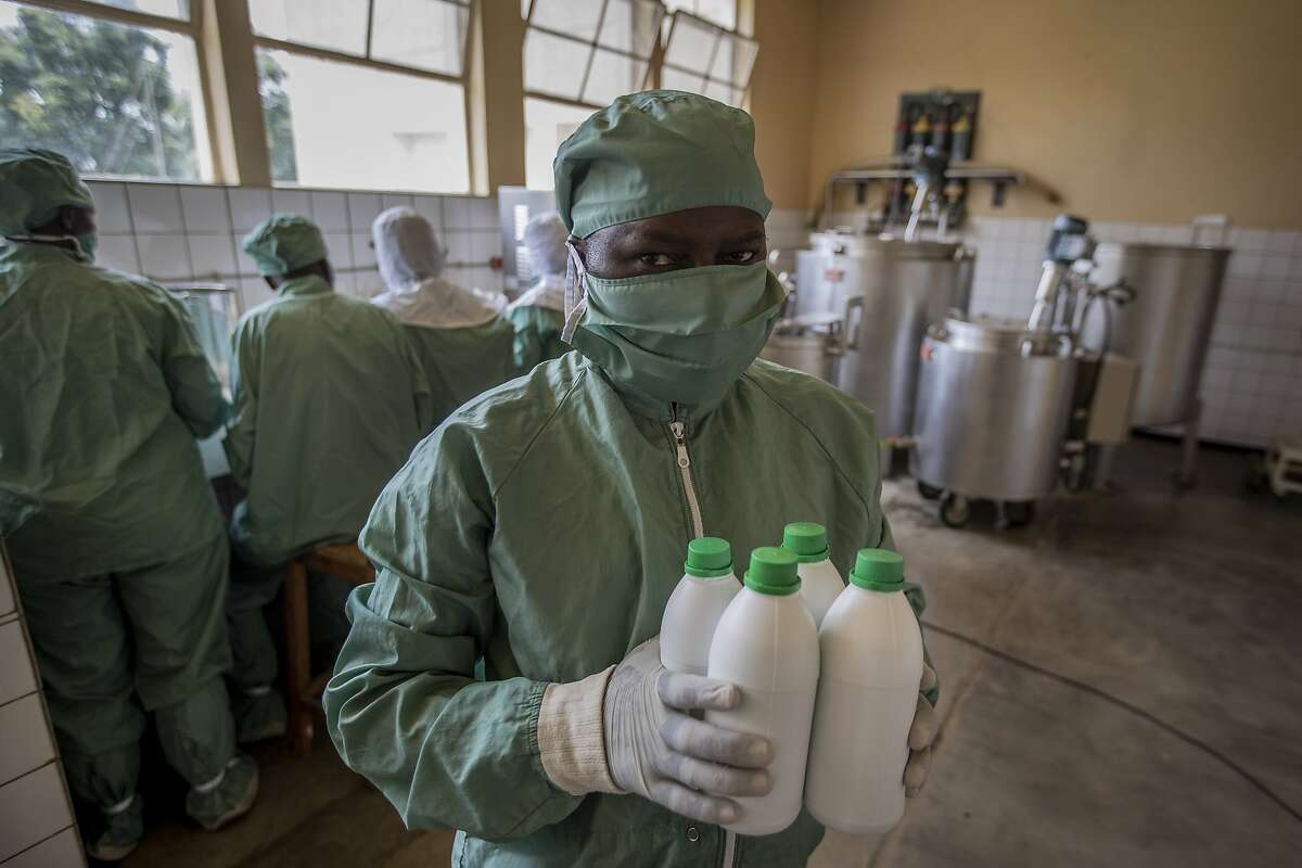 In this photo taken Thursday, Nov. 7, 2019, a worker carries bottles of liquid morphine after making it from powder, wearing protective clothing to protect from the effects of the drug and to prevent contamination, at the Pharmaceutical Laboratory of Rwanda in Butare, Rwanda. While people in rich countries are dying from overuse of prescription painkillers, people in Rwanda and other poor countries are suffering from a lack of them, but Rwanda has come up with a solution to its pain crisis - it's morphine, which costs just pennies to produce and is delivered to households across the country by public health workers. (AP Photo/Ben Curtis)