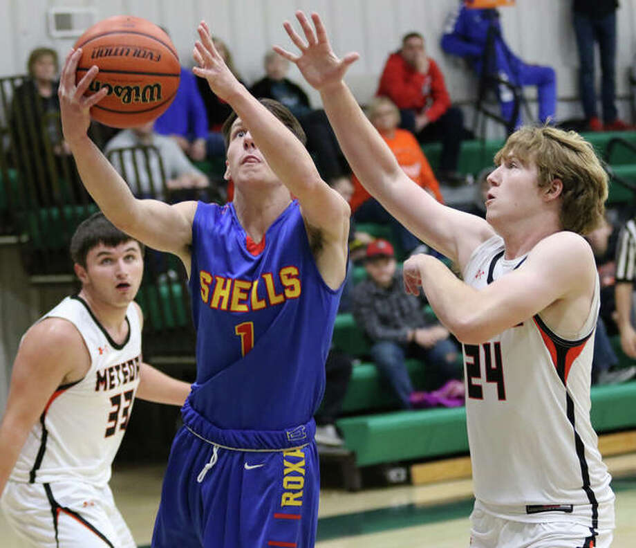 Roxana's Drew Beckman goes up to score after splitting Marissa defenders Logan Jones (right) and Clayton Cohoon (left) during a Shells win at the Metro-East Lutheran Tournament on Nov. 29. The Shells are back in tourney play this week at Pinckneyville. Photo: Greg Shashack / The Telegraph
