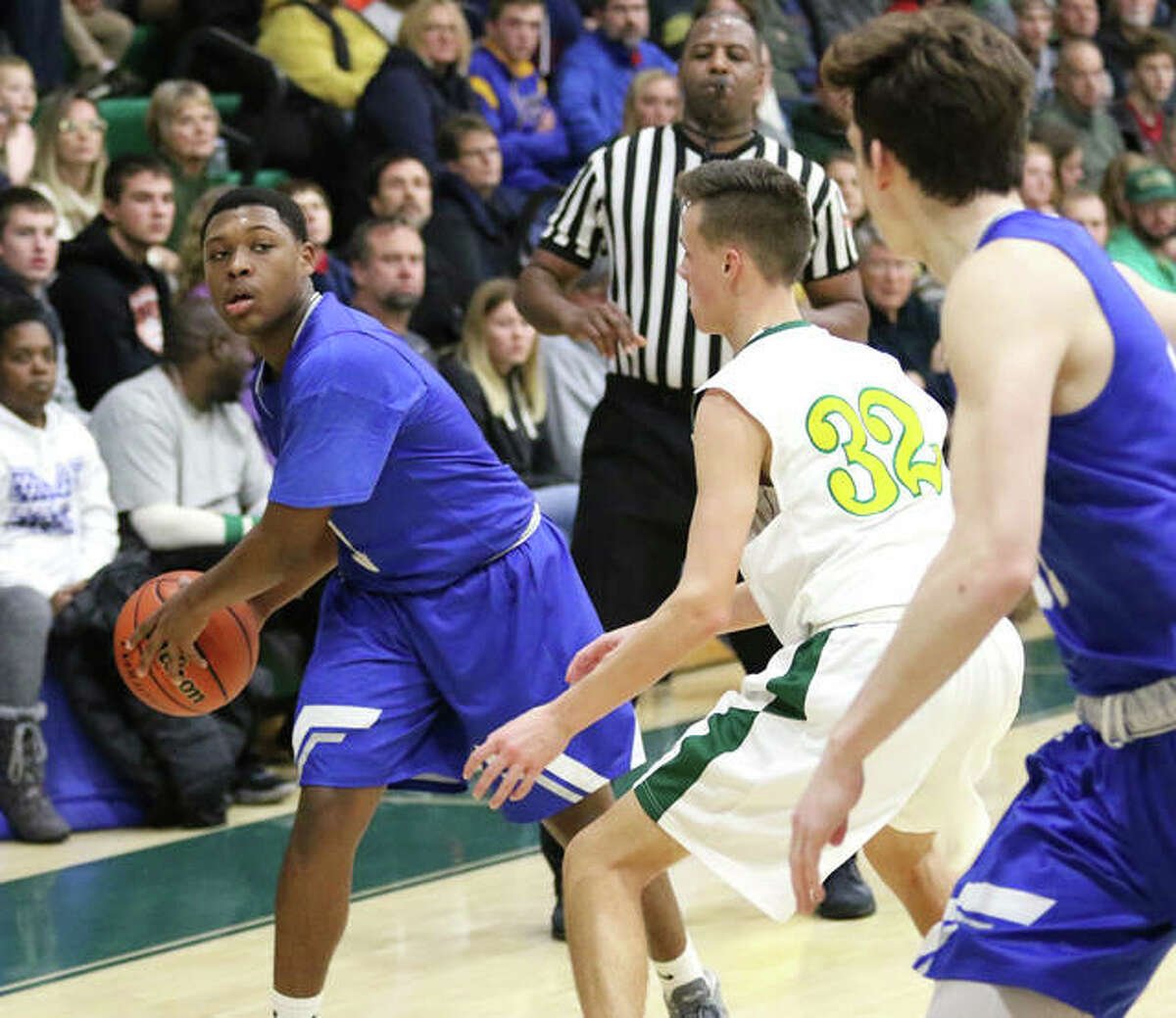 Marquette Catholic's Iggy McGee (left) looks to pass to teammate Spencer Cox while Metro-East Lutheran's Elliott Wilson defends during a Nov. 19 game at the MEL Tourney in Edwardsville.