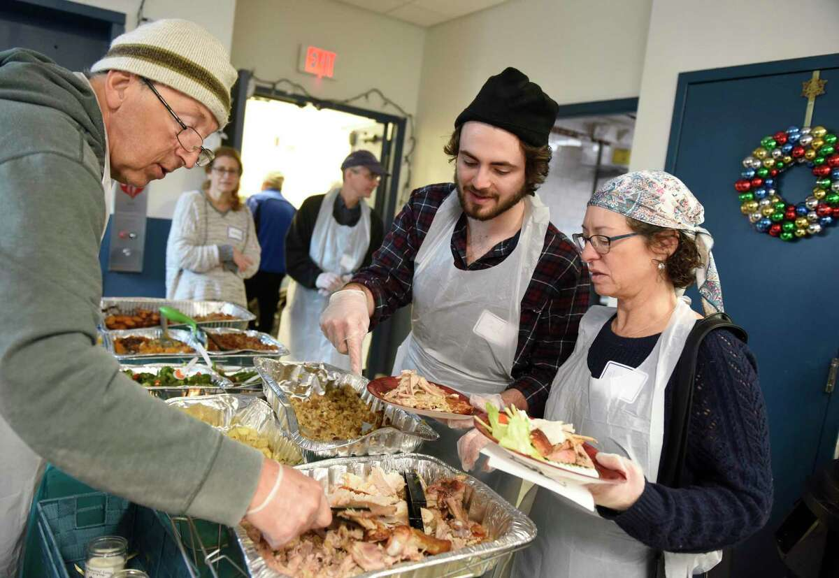Congregation Agudath Sholom volunteers Joseph Rubbak, left, Zach Smart, center, and Michal Smart serve lunch on Christmas Day to homeless Stamford residents at Pacific House in Stamford.