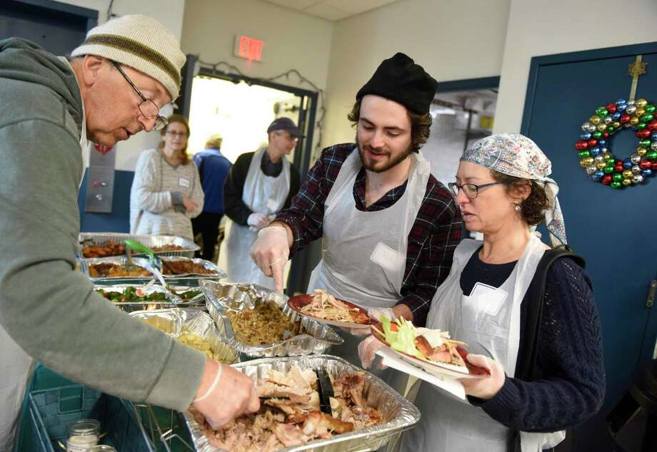 Congregation Agudath Sholom volunteers Joseph Rubbak, left, Zach Smart, center, and Michal Smart serve lunch on Christmas Day to homeless Stamford residents at Pacific House in Stamford. Photo: Tyler Sizemore / Hearst Connecticut Media / Greenwich Time