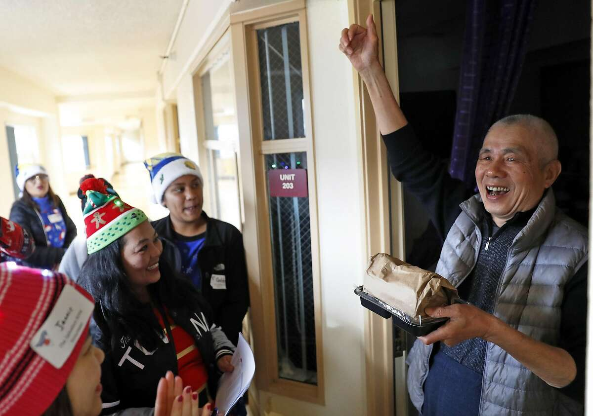 Ceatrice Polite Apartments' resident Qing Mei excitedly accepts a Christmas dinner from Salvation Army volunteer Joyce DeWitt and 17 other members of her family in San Francisco, Calif., on Wednesday, December 25, 2019.