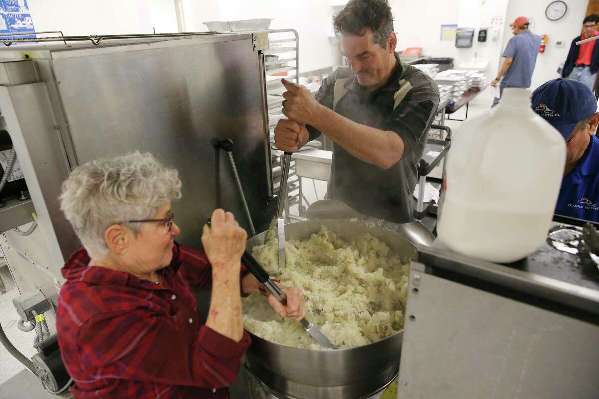 Ann Winer (from left) and Dan Klein whip up mashed potatoes Wednesday so other volunteers from the Jewish congregation of Temple Beth-El could deliver meals to first responders working on Christmas Day at 55 police and fire stations across Bexar County.