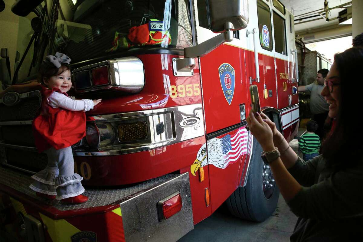 Sawyer Penner, age 14 months, gets her picture taken by her mother, Karly, while the toddler was standing on a fire truck at Fire Station No. 10 on Culebra Road. The were among the members of the Jewish congregation of Temple Beth-El who provided meals Wednesday to first responders who had to work on Christmas Day at 55 police and fire stations across Bexar County.