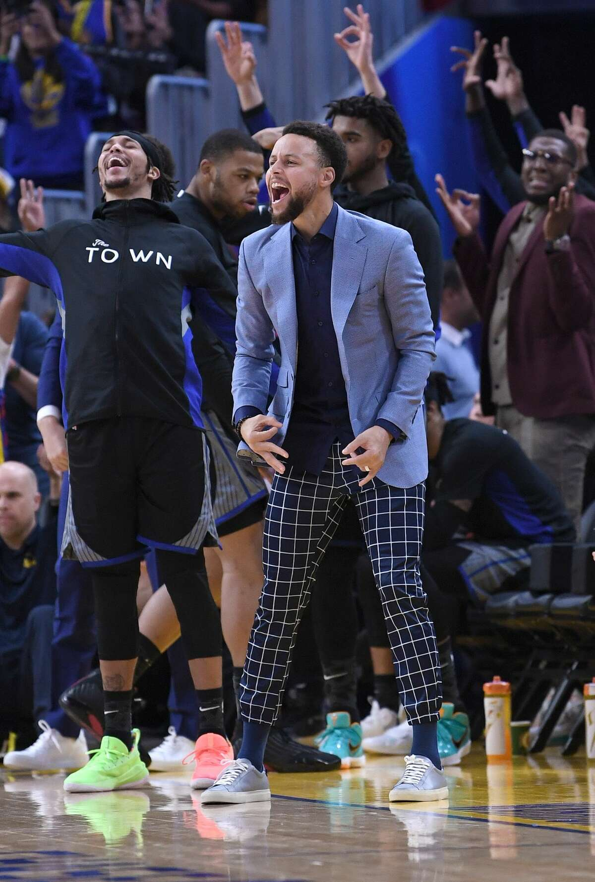 FILE PHOTO: Stephen Curry #30 of the Golden State Warriors celebrates off the bench after Draymond Green #23 made a three-point shot against the Houston Rockets during the second half of an NBA basketball game at Chase Center on December 25, 2019 in San Francisco, California. Curry was seen enthusiastically cheering on his team from the bench as the Warriors won their fourth game in part of a winning streak.