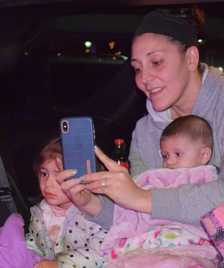 Angela Cosban keeps her little ones Gabriella, 2, Jianni, 3 months, and Giuliana, 6, not shown, warm in her car as they view the Parade of Lights from the hatchback of their vehicle. Photo: Deborah Rose / Hearst Connecticut Media / The News-Times  / Spectrum