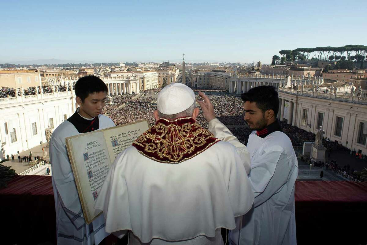 Pope Francis blesses faithful from the balcony of St Peter's basilica during the traditional