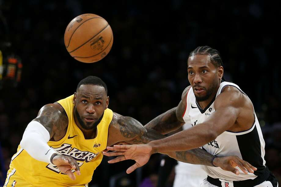 The Lakers' LeBron James, left, and Clippers' Kawhi Leonard (2) chase the ball during the second half of an NBA basketball game Wednesday, Dec. 25, 2019, in Los Angeles. The Clippers won 111-106. (AP Photo/Ringo H.W. Chiu) Photo: Ringo H.W. Chiu / Associated Press