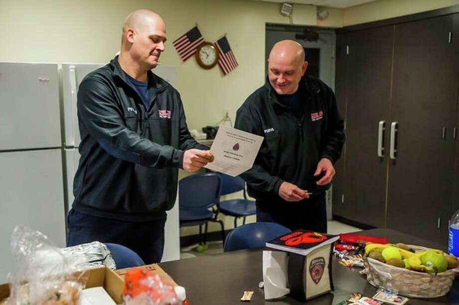 City of Midland firefighters Nick Petrillo, left, and Justin Purvis, right, read a card that was delivered as part of a large donation of food from residents of Washington Woods Tuesday morning at fire station #1. (Katy Kildee/kkildee@mdn.net)