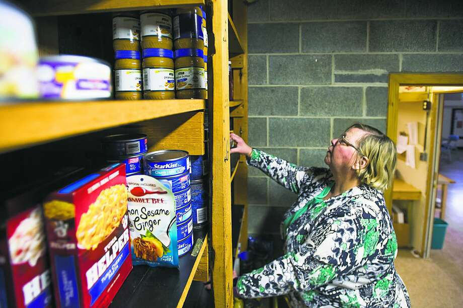 Kathy Nogaski pulls food items from shelves as she assembles an order for a family inside the Sanford Pantry Tuesday morning. The pantry is located inside Sanford United Methodist Church and is one of eight pantries supported by the Midland County Emergency Food Pantry Network. (Katy Kildee/kkildee@mdn.net) Photo: Katy Kildee/kkildee@mdn.net