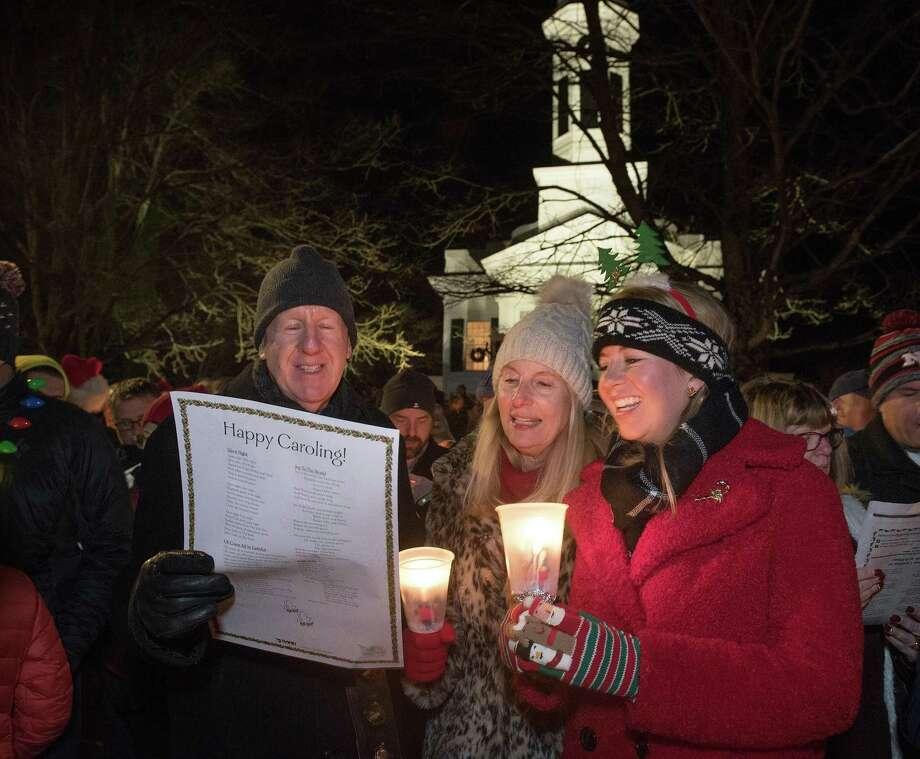 Steve, Emma and Lorraine Zaretsky sing carols on Christmas Eve on God's Acre in New Canaan, Conn. Photo: Bryan Haeffele / Hearst Connecticut Media / BryanHaeffele