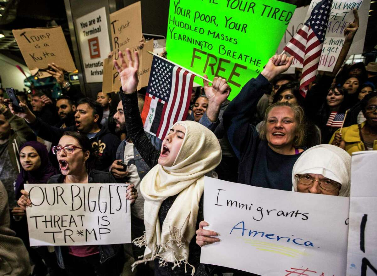Demonstrators protest against President Donald Trump's executive orders on immigration and refugees at Houston's George Bush Intercontinental Airport in January 2017. Since then, his administration has slashed the number of refugees allowed here in 2020 to a historic low of 18,000 and required state and local authorities consent to their resettlement.