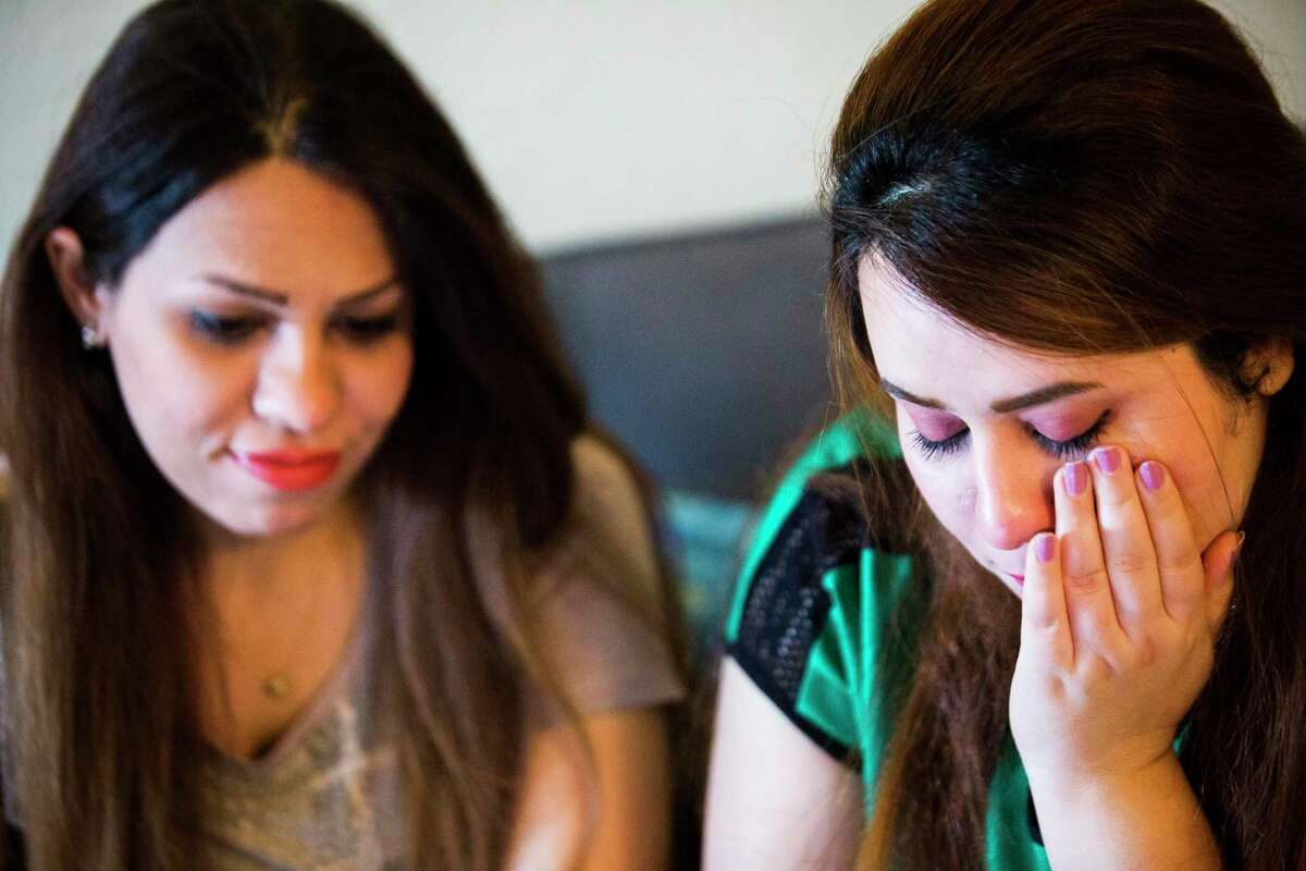 Sarah Ismaeil, left, 31, and her sister Dhuha Ameri, 26, become emotional while they speak with their parents in Iraq using a video chat application from Houston in August 2018. The sisters have been waiting for two years for their parents to be able to join them in the United States. The entire family applied for refugee status and everyone was granted the protection, except, their parents' applications stalled due to the Trump administration's changes to the refugee system.