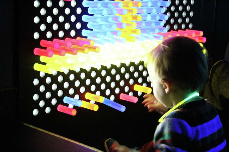 Lockland plays with the neon pegs at the Children's Museum during the 3rd annual Glow Mania New Year's event. Photo: Photo By: Erica Apodaca/ The Enterprise / Erica Apodaca/ The Enterprise