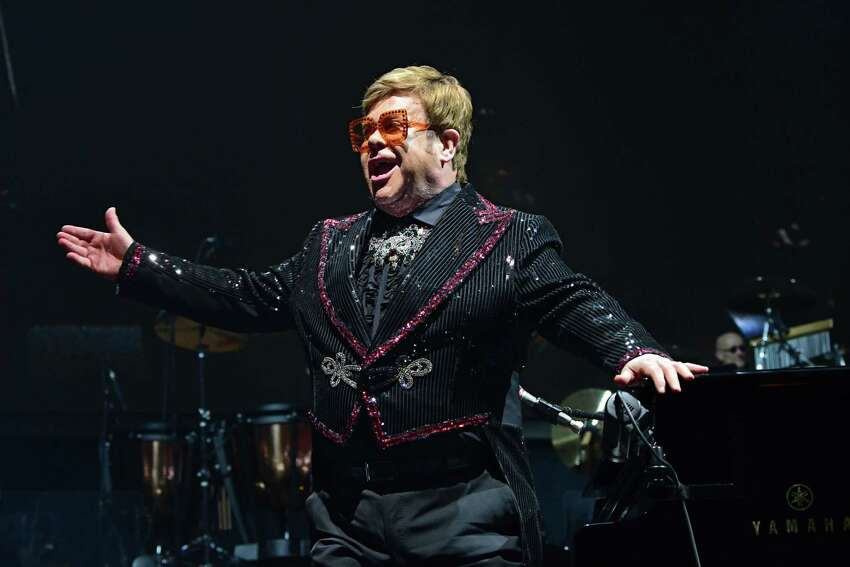 Elton John stands after opening his show with