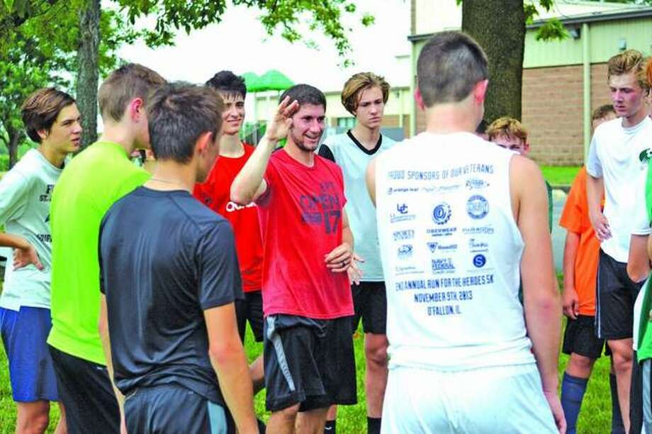 "Father McGivney soccer coach Tim Vance, middle, talks to his players during a ""kick-around"" practice session in July 2018."